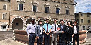 """Matteo Ricci insieme alla delegazione cinese in piazza del Popolo con in mano il logo """"We Pesaro"""""""