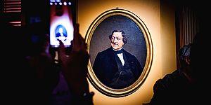 Persona con in mano un cellulare mentre fotografa il ritratto di Gioacchino Rossini