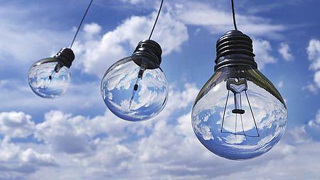 Tre lampadine trasparenti appese nel cielo tra le nuvole