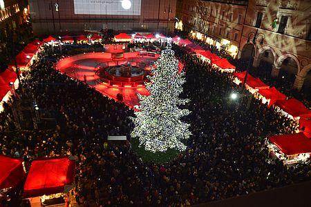 albero e bancarelle della piazza illuminate