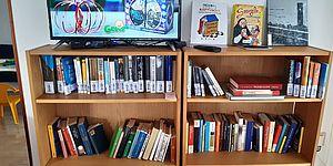libreria con libri e sopra televisione