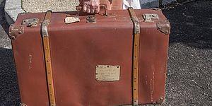 Immagine di valigia tenuta da una mano maschile