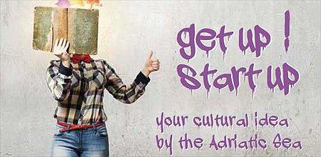 a six ragazza in piedi con libro e a dx parete con scritte spruzzate