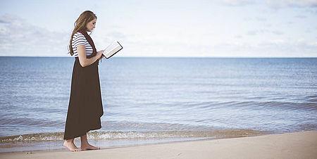 Fotografia di una donna che legge in riva al mare