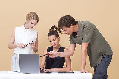 tre persone intente a guardare un pc
