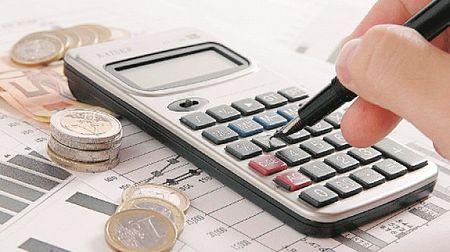 Calcolatrice, monete ed una mano con penna