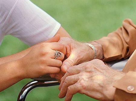 immagine che ritrae mani di persona anziana che si appoggia a supporto con l'aiuto di un'altra persona