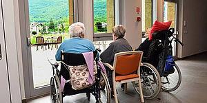 Anziani in carrozzella che guardano fuori da una vetrata