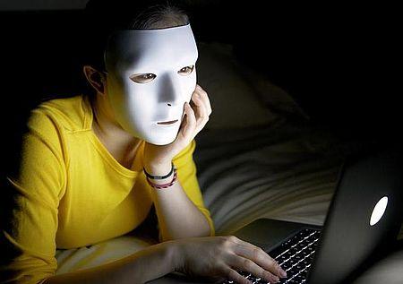 paticolare immagine locandina raffigurante ragazza davanti a un computer con maschera in volto