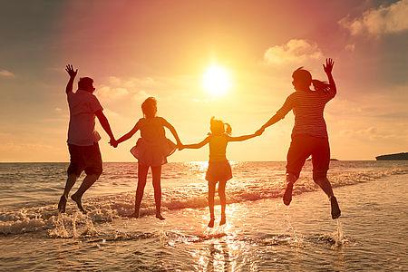 Foto famiglia al tramonto sulla spiaggia