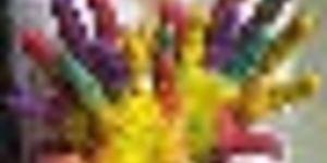 mani di bambino che si incrociano colorate con vernice