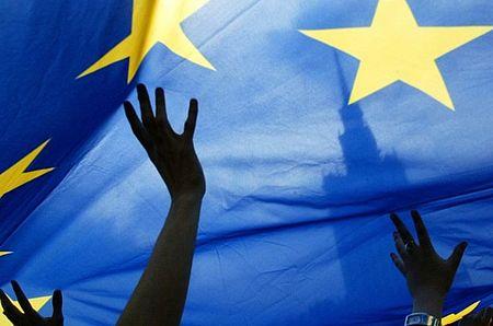 particolare bandiera europea con delle mani che la sorreggono