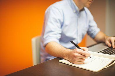 Persona che scrive su computer e con penna su quaderno