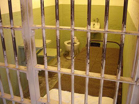 immagine di una cella con sbarre letto, bagno