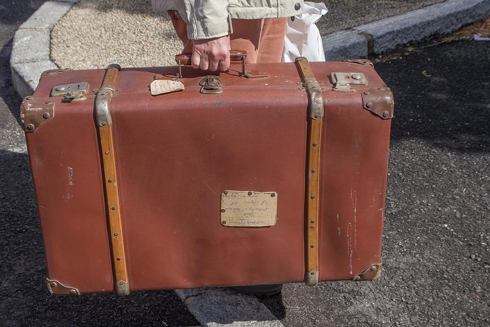 Immagine di valigia tenuta da una mano maschilea valigia