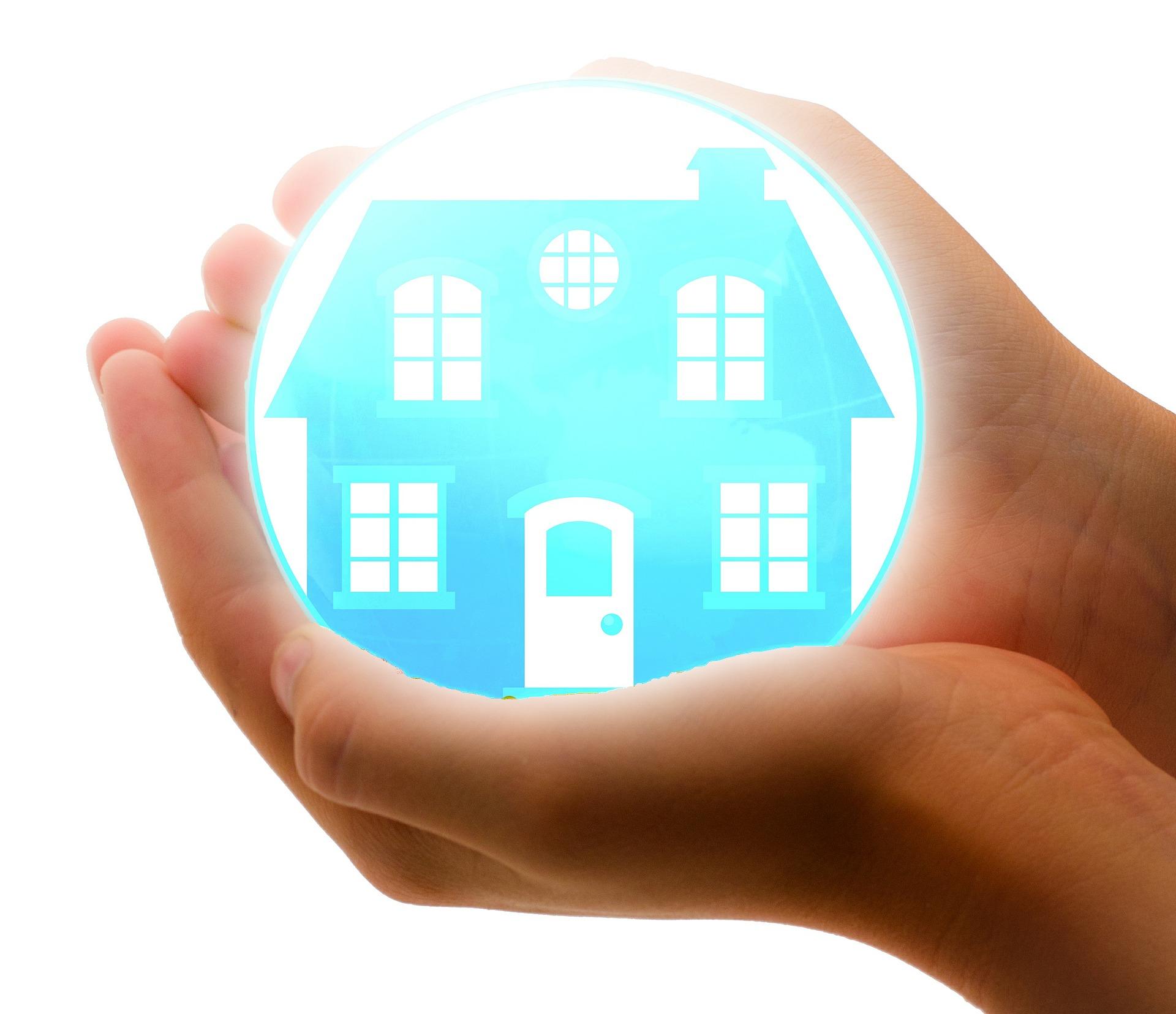 mani che racchiudono palla di vetro con casa