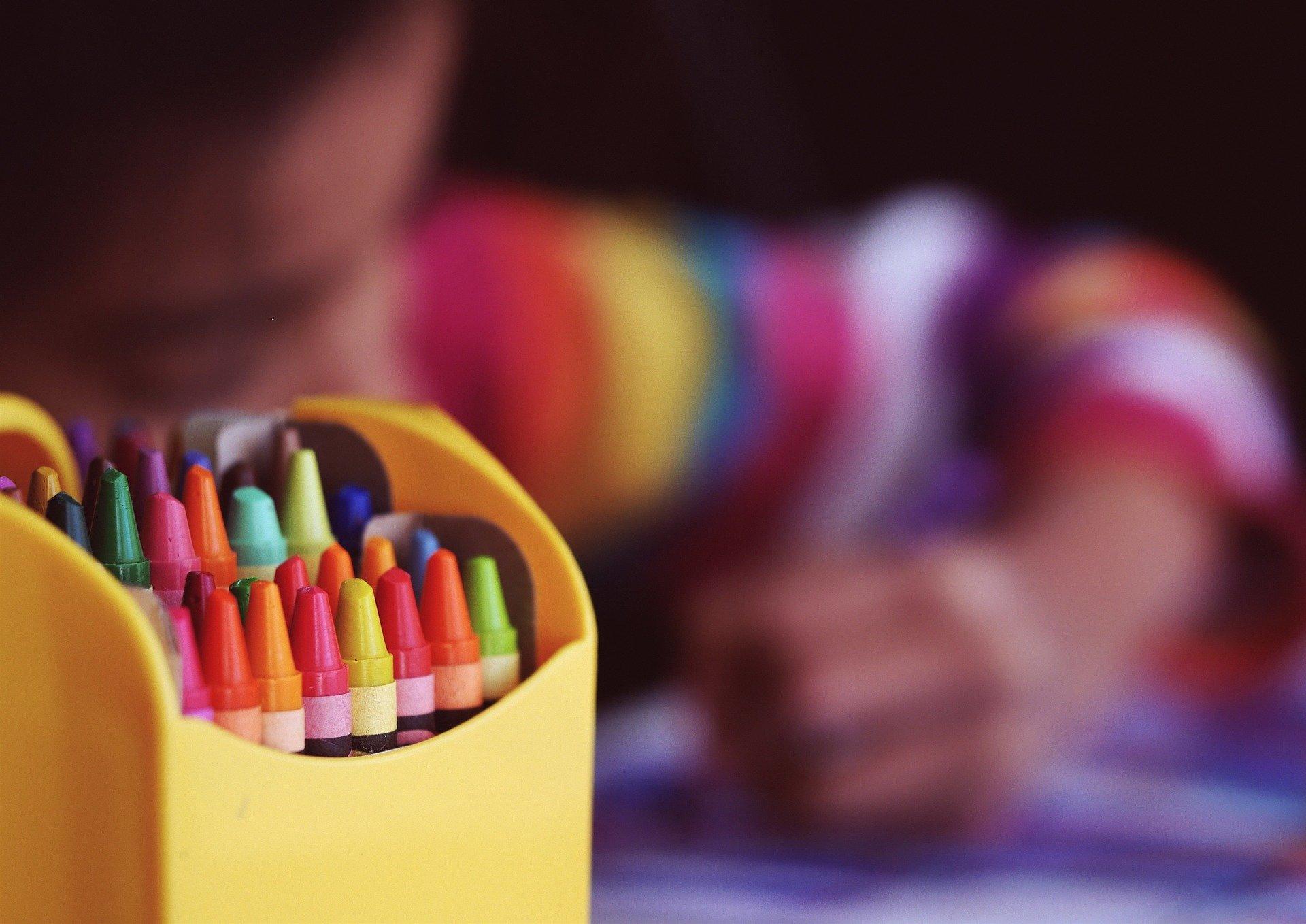 scatola di colori a cera e bambino che disegna