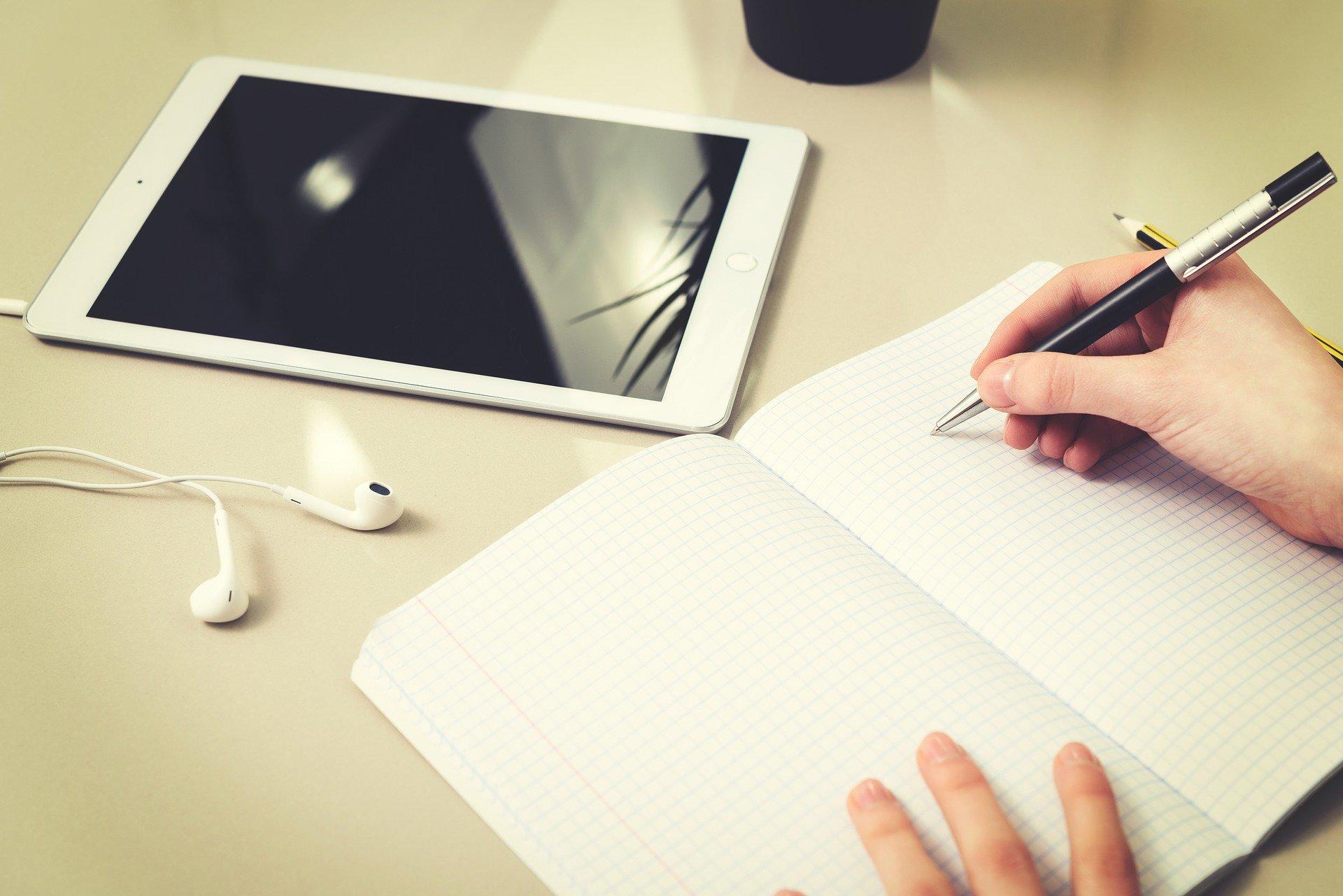 scrivania con tablet e quaderno